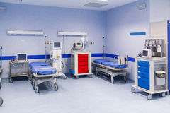 Hospital room with beds. Two blue covered hospital beds await the next patients. Blood pressure equipment and medical scanners Stock Image