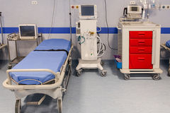 Hospital room with beds. A blue hospital bed awaits the next patients. Blood pressure equipment and medical scanners royalty free stock photo
