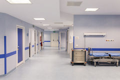 Hospital room with beds. A blue hospital bed awaits the next patients. Blood pressure equipment and medical scanners stock photography