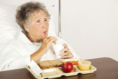 Hospital Senior Has Lunch. Senior woman in the hospital, eating lunch and drinking from a straw Stock Images