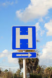 Hospital sign. Blue and white hospital sign with arrow pointing in direction of hospital Royalty Free Stock Photography