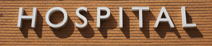 Hospital sign on medical center. With hard diagonal shadows on brick wall background Stock Photography