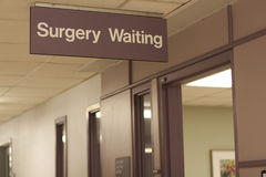 Hospital sign: Surgery Waiting. A hallway or corridor in a hospital with a Surgery Waiting room sign and doorway Stock Images
