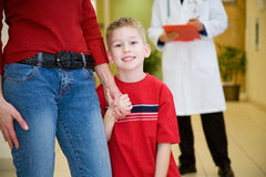 Hospital: Smiling Boy Holds Mother's Hand Before Meeting Doctor Royalty Free Stock Photos