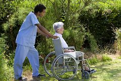 Hospital staff member pushing a happy senior patient. Young hospital staff pushing  happy senior patient in wheelchair outdoors Royalty Free Stock Images