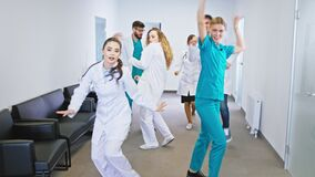 Hospital stuff group of doctors and nurses in front of the camera dancing excited and looking straight to the camera
