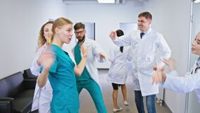 Hospital stuff of nurses and doctors dancing excited in front of the camera they feeling very happy and smiling large
