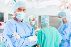 Hospital surgeons operating in operation room Stock Images
