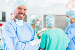 Hospital surgeons operating in operation room Stock Image