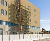 Hospital under construction. New hospital building under construction with earth-movers and fencing in foreground. All logos have been removed Royalty Free Stock Images