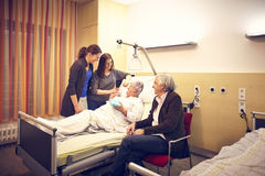 Hospital visit family. With patient in bed Royalty Free Stock Image