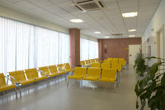 Hospital waiting area with yellow metallic chairs. Stock Image