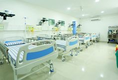 HOSPITAL WARD INTERIOR. A Private calm hospital ward interior,  neatly arranged with beds in a white background to add peace the space Royalty Free Stock Photography
