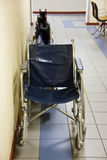 Hospital wheelchairs. Wheelchairs parked on the side of a hospital hallway Stock Photos