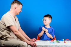 Hospital worker. Medicine concept. Kid little doctor sit table medical tools. Illness treatment. Dad and son medical. Dynasty. Health care. Medical examination royalty free stock photo
