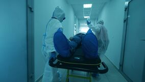 Hospital workers transport a patient with coronavirus on stretcher. Coronavirus covid-19 Infected Patient in a clinic.