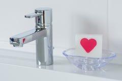 Hospitalidade no banheiro, sabão com coração vermelho Imagem de Stock