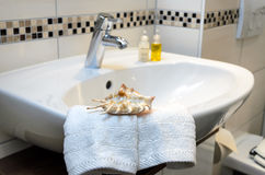 Hospitality in the bathroom. White bathroom sink with a wonderful arrangement of white flannels and a shell Royalty Free Stock Photos