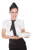 Hospitality hostess presenting a voucher. Smiling welcoming hospitality hostess presenting a voucher in her hands isolated on white stock photos