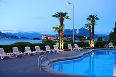 Luxury hotel, Lago Maggiore, Italy. Swimming pool. Luxury accommodation and hospitality. Five star hotel swimming pool at dusk with view on the Isola Bella, Lake royalty free stock photo