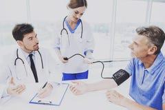 Hospitalizado femenino del doctor Measures Blood Pressure Fotografía de archivo libre de regalías