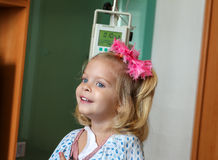 Hospitalized Girl. Recovering Little baby girl hospitalized with a Intravenous bag on a pole. Real situation Royalty Free Stock Photography