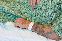 Hospitalized man's arm with ID bracelet. The tattooed arm of an elderly man who is in a hospital bed.  His hospital identification band is visible.  He wears a Stock Photo