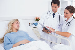 Hospitalized woman and doctors. Hospitalized women and doctors standing next to her Stock Photography