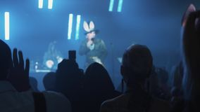 Host in mad hatter costume talk to crowd in night clup at halloween party. Host in mad hatter costume with bunny ears talk to crowd from scene in night clup at stock footage