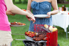 Host serving meals on barbecue party Stock Photography