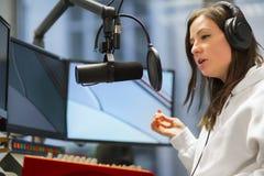 Host Talking On Microphone In Radio Studio. Young female host talking on microphone while wearing headphones in radio studio Stock Photography