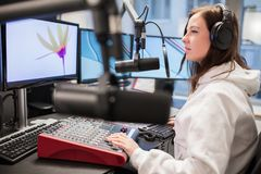 Host Using Headphones And Microphone While Looking At Monitor. Side view of female host using headphones and microphone while looking at monitor in studio Royalty Free Stock Photo