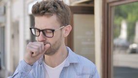 Hosta den sjuka unga mannen som står utomhus- lager videofilmer