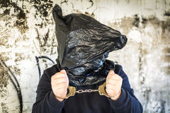 Hostage in handcuffs. And with a bag on head near wall Royalty Free Stock Photography