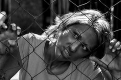 Hostage. Woman taken hostage with her hands clinging to the grates of a mesh with an expression of hatred for his captors. Concept: lack of human rights Royalty Free Stock Photos