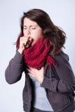 Hostande flicka i halsduk fotografering för bildbyråer