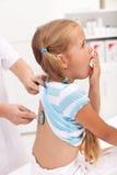 Hostande liten flicka på doktorn Arkivbild