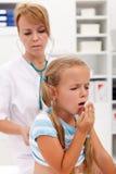 Hostande liten flicka på vård- checkup Fotografering för Bildbyråer