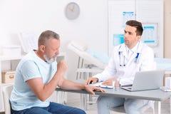 Hostande mogen man som besöker doktorn arkivbilder