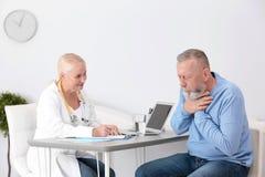 Hostande mogen man som besöker doktorn arkivfoton