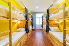 The hostel dormitory beds arranged in room. Hostel dormitory beds arranged in room stock photos