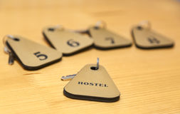 Hostel. The keys of several rooms of a hostel are on a wooden table. Selective focus Royalty Free Stock Image