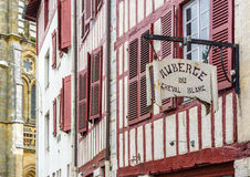 Hostel signboard in a facade of typical building of Aquitaine. Stock Photos