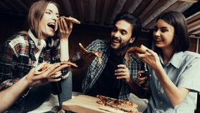 Friends laugh, hold Pizza slices and eating stock photography