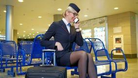 Hostess bionda che chiacchiera sul telefono nel corridoio di partenza stock footage