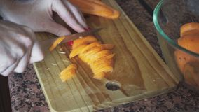 The hostess cuts carrots with a knife on a wooden board.  stock video