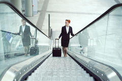 Hostess on escalator in airport. Job and travel concept Royalty Free Stock Photo