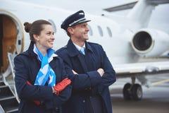 Hostess felice e pilota che individuano vicino all'aeroplano fotografia stock