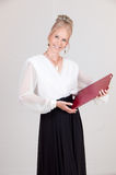 Hostess Holding Menu. Elegantly dressed smiling attractive female restaurant Hostess holding a red menu in an assertive greeting pose on a white background Stock Photo