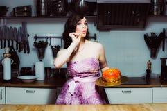 Hostess holds cake like big donut with fondant. Hostess holds cake like big donut with red fondant stock images